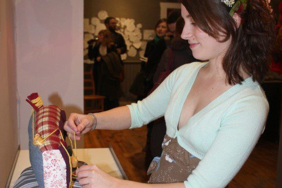 Katie Sorrell, 22, makes a final adjustment to her piece during the opening of 'DiWhy?'. Craft exhibits, such as this one at the OCC, are helping alert the public that crafts are comparable to art.
