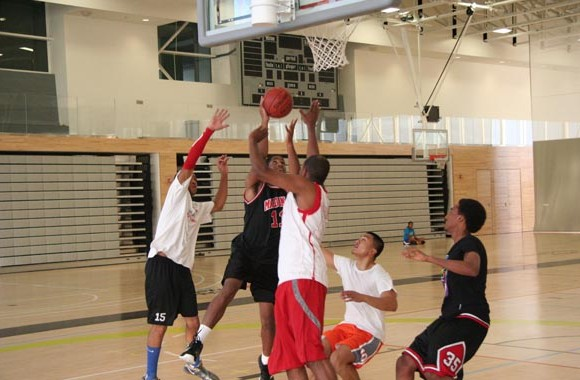Centennial Colts hopefuls try to finish at the rim in a 3-on-2 drill during try-outs