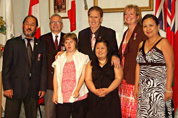 Tobias Enverga (far left), MP Corneliu Chisu, Dr. Ashleigh Molloy (centre) with Lindsey Molloy and Rocel Enverga (centre), MPP Tracy Mac Charles (right) and  Enverga's wife Rosemer Albovias (far right) at the  Investiture of the Queen's Diamond Jubilee Medal ceremony in July, where both men received medals for their community service.
