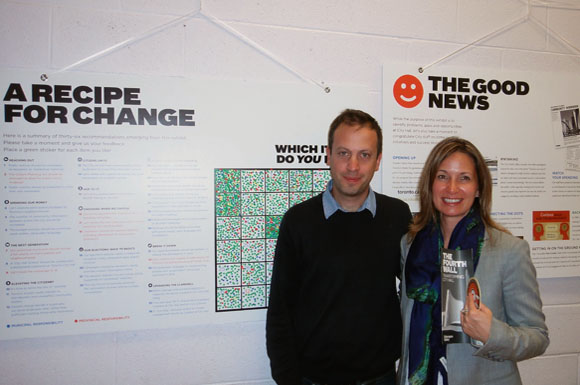 Dave Meslin and Councillor Michelle Berardinetti of Ward 35 stands in front of the dot grid that marks all 36 recommendations for change. People stick a dot sticker on the suggestion they want to see happen the most.