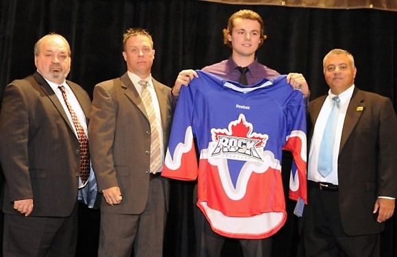 Newly selected defenceman Bradley Kri [middle] poses with Terry Sanderson, Troy Cordingley and NLL Commissioner George Daniel after he becomes the Toronto Rock's first choice in the 2012 NLL draft.