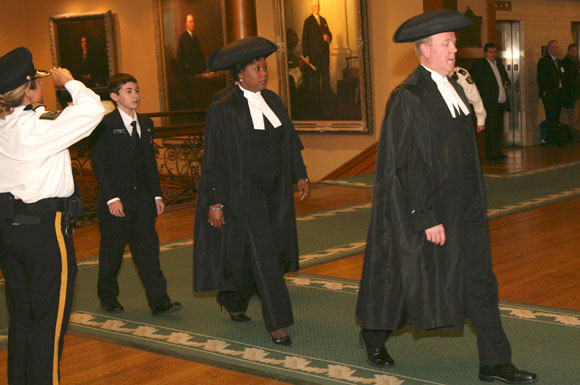 Liam Donnelly (left) takes his turn as Page Captain for the day. He follows the ceremonial procession of the Speaker, Head Clerk and other officials into the chamber  to begin the day.