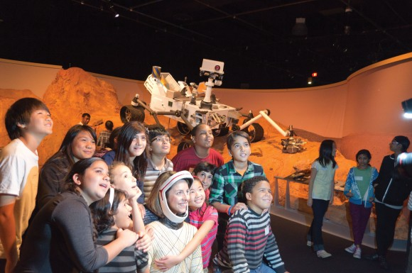 "Grade 6 students from Forest Manor Public School pose with a full-size model of the Mars rover Curiosity, at the Ontario Science Centre's new exhibition, ""Beyond Planet Earth: The Future of Space Exploration,"" running until Jan. 1."