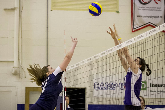 Varsity Blues' Sarah Chapin lobs a ball over a defending Mustang during OUA action on Friday