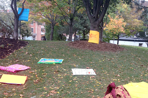 Signs belonging to some of the roughly 40 people gathered at St. James Park earlier today mark the spot where Occupy Toronto set up camp a year ago. A march scheduled for 1 p.m. was cancelled.