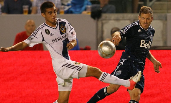 Whitecaps' Jordan Harvey attempts to defend against Galaxy's Hector Jimenez