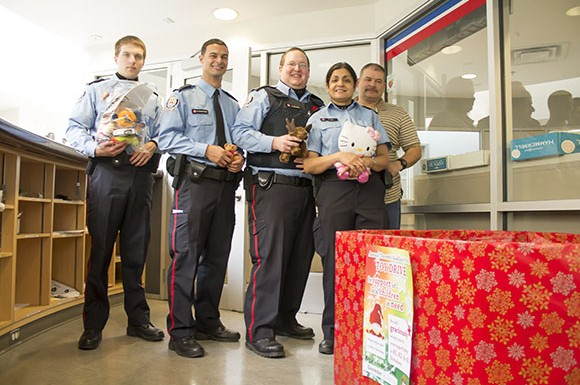 "Toronto police are asking for donations of new toys to ""help give a child a Christmas,"" the promotional poster says. Left to right: Auxiliary Liaison officers Marc Calaerese, Daniel Muscat-Dargo, Lance McGuire, Rangi Puri, and Police Constable Guy Service."