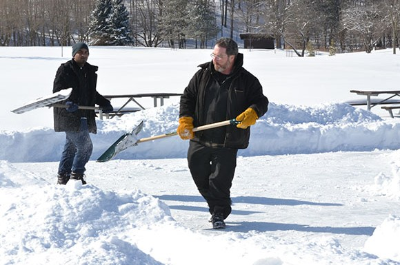 Active community member and seasoned outdoor rink builder Brian MacFarlane (right) along side an environmental science student shovels snow off of the rink.
