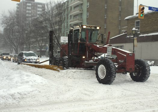 Snowplow clears intersection of Pape and Cosburn avenues  during storm lull around 4 p.m. Friday.