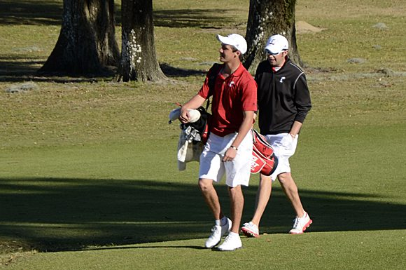 University of Cincinnati golfer Michael Wolf and assistant coach Andrew Stephens head to the last green at the Lake Jovita Golf and Country Club at Dade City, Florida, Monday.