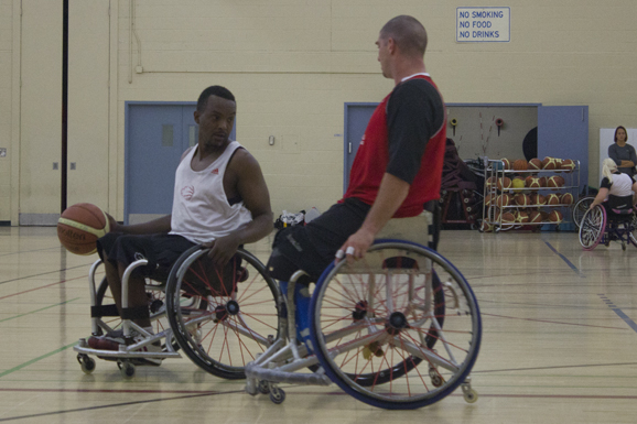 Abdi Dini, 32, attempts to dribble past teammate Adam Lancia, 33, in a open practice at the launch of the Wheelchair Basketball Canada Academy. Dini, a Paralympic gold medal winner and Scarborough local is set to train full-time at the academy.