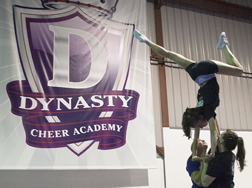 Stephanie Purves, Trisha Shechuck (in the air), and another teammate practise one of their skills.   The Dynasty Cheer Academy will be competing at the PCA Nationals on Nov. 29.