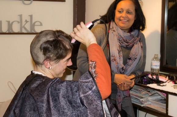 Maddie Newell takes a turn shaving her own head as her hairdresser, Gina Edmonds watches.