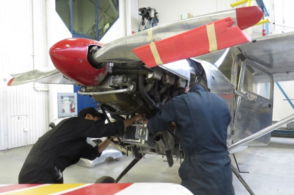 Students in the aerospace program are hard at work fixing this plane's engine.