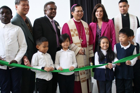 Children from Blessed Pier Giorgio Frassati Catholic School join, from back left, TCDSB trustee Garry Tanuan, MPP Bas Balkissoon, Bishop Nguyen and Principal Cherrier for the ribbon cutting.