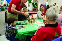David Lewis, standing, helps his grandchildren build a gingerbread house at Habitat for Humanity's annual Gingerbread Build on Dec. 8.