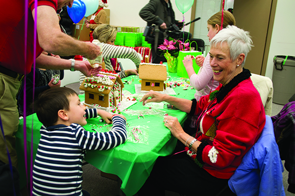 Five-year-old Oliver Lewis (left) and his grandmother Tillie Lewis give each other a loving smile as they decorate a gingerbread house for Habitat for Humanity.