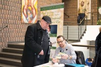 Kevork Tikjian selling a New Year's Eve party ticket to a member of the Armenian Community Centre.