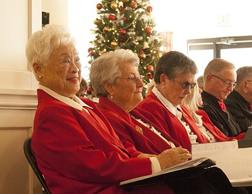 Wilma Chang, a member of The Scarborough Village Singers, smiles while watching the audience enjoy the Christmas carols.