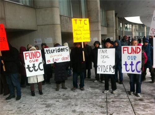 TTC riders protest outside Toronto City Hall.