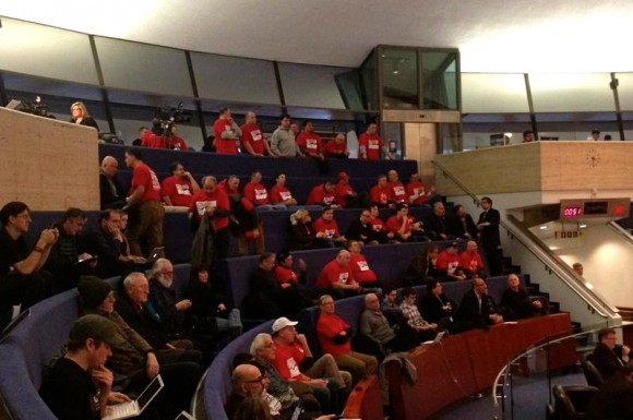 Members of the Toronto Firefighters Association line the viewer's balcony at city hall.