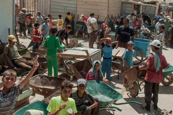 Syrian refugee children line up for work in Za'atari refugee camp in Jordan.
