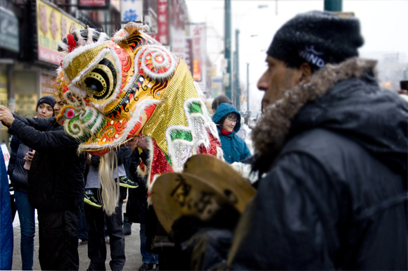 Members of the Hong Luck Kung Fu Club's lion dance team perform along Spadina Avenue Saturday. The club is 53-years-old and is Toronto's oldest kung fu school. In the background, curious passersby stop to take a 'selfie' with the performers.