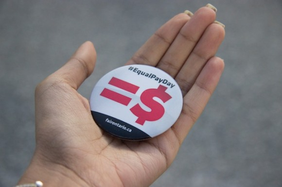 Individuals handed out pins and brochures at Queen's Park for Equal Pay Day.