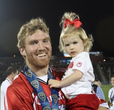 Merrill celebrates winning the 2014 FIL World Lacrosse Championship for Canada this past July with his two-year-old daughter Sawyer.