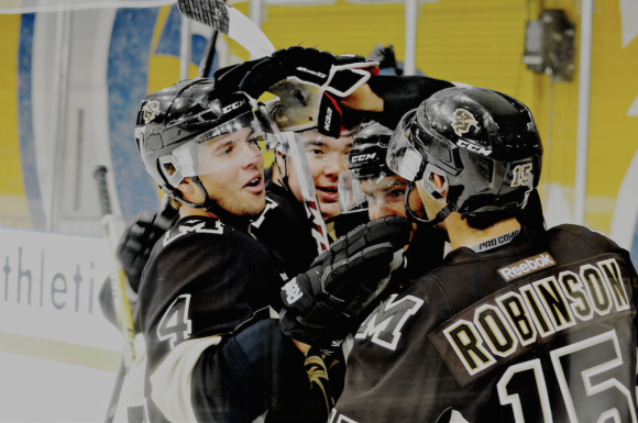 From left to right: Reid Gow, Rene Hunter, and Chad Robinson celebrate a goal in a 5-4 Bisons win.