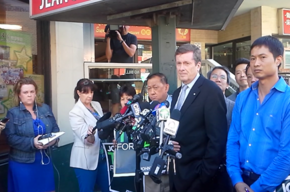John Tory talks to reporters besides David Chen (front right) in Chinatown on Thursday.