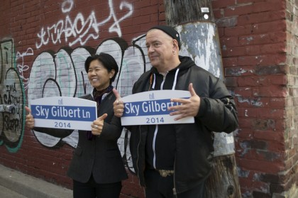 Krisytyn Wong-Tam (left) and Sky Gilbert (right) posses with personalized signs.