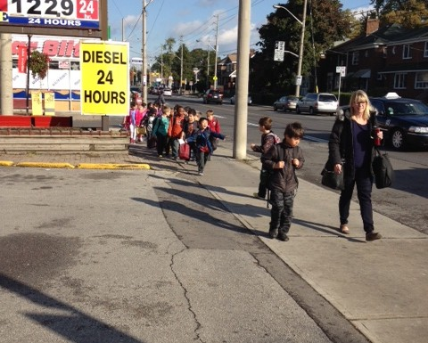 Students from William Burgess elementary walk to evacuation centre along Pape Avenue Wednesday.