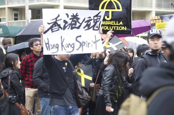 A student holds a  place card in support of Hong Kong protests at a demonstration held by the Ontario United Front of Hong Kong Students