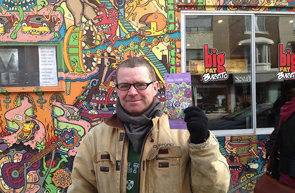 Al Runt holds up the Ride Guide he designed as he stands outside Lee's Palace whose mural he also created.