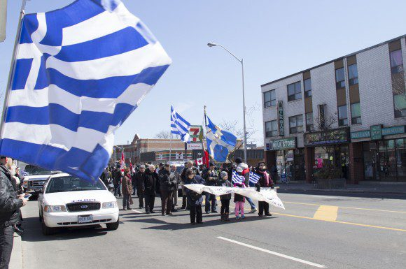 The parade begins to take shape, as thousands lining up the Danforth clap and wave Greek flags.