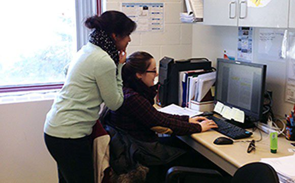 Teaching assistant Samantha Stefanoff works one-on-one with student Tehmeena Chaudhry during school strike.
