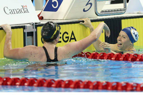Rachel Nicol and Kierra Smith celebrate at the wall after finishing first and second in the 100 metre breaststroke