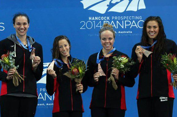Katerine Savard (second from left) celebrating with teammates Chantal Van Landeghem, Kierra Smith, and Brooklynn Snodgrass at the 2014 Pan Pacific Championships in Queensland, Australia last August