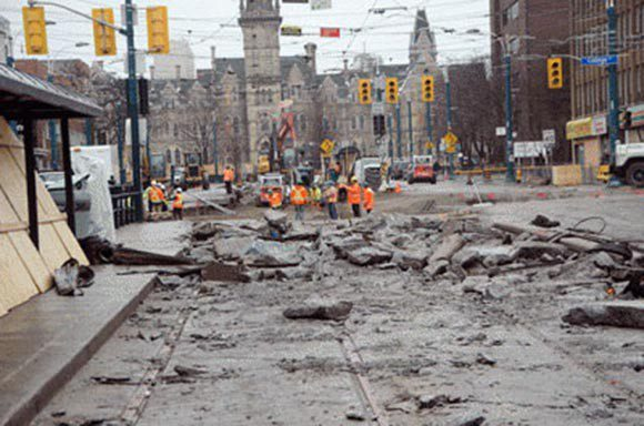Workers resurface the road at College Street and Spadina Avenue.