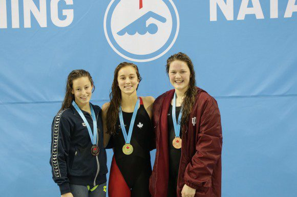 Emily Overholt poses alongside competitors Katerine Savard and Kennedy Goss at the Canadian Swim Trials, Wednesday night.