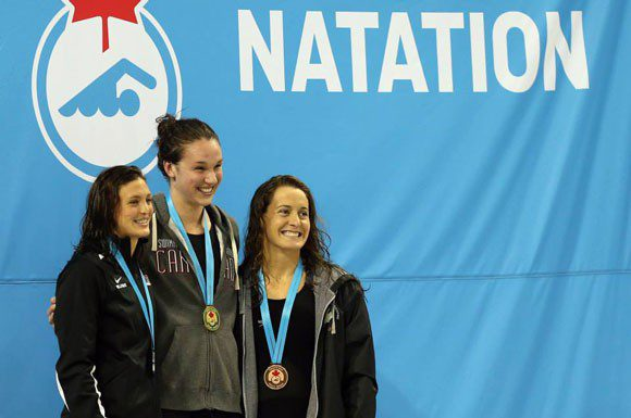 Chantal van Landeghem, Michelle Williams and Sandrine Mainville pose with their medals from the 50 metre freestyle on Saturday night.