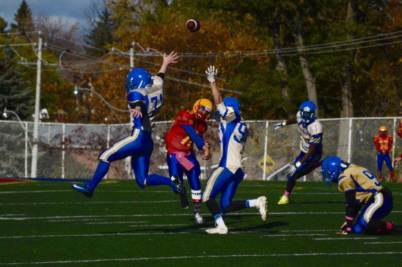 Northern Red Knights quarterback Teshaun Tran (10) fits a pass between two members of the Birchmount Park Panthers defence.