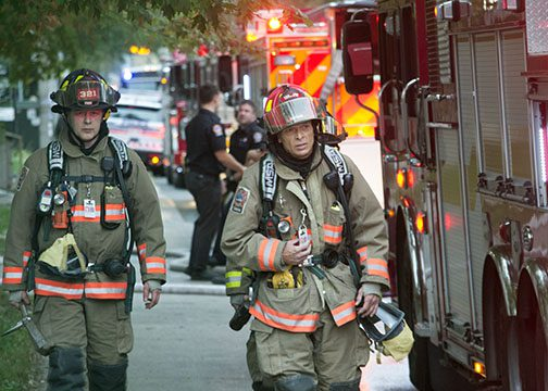 Fire fighters leave the building after extinguishing two-alarm fire early Monday morning.