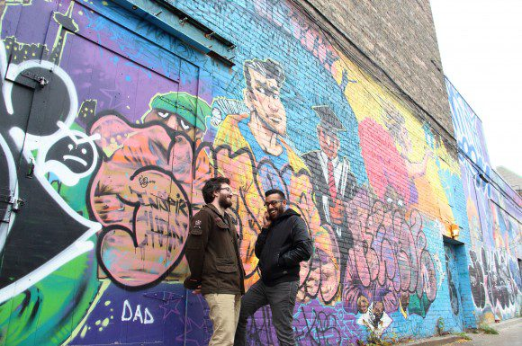 Author Kade Davies, left, with artist Yawar Raja in front of a graffiti on Bloor and Bathurst. To the pair, this wall best represents what Toronto means to them. Last week marks the fifth year anniversary of science fiction project The Solid Intangibles.
