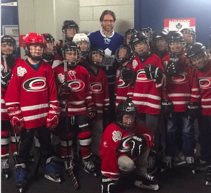 Shayne Corson posing with the Clarkson Hurricanes as the special guest for blue and white day at the Hershey Centre.