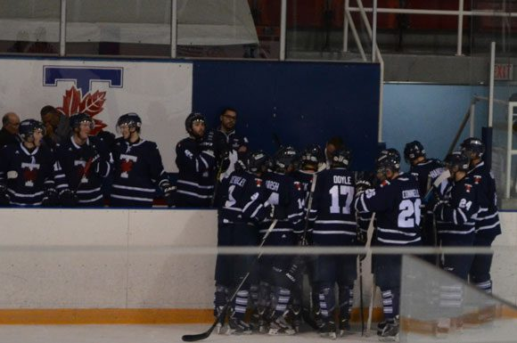 The Varsity Blues gather at the bench during a Laurier timeout late in the third period.