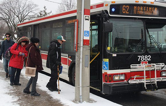 Commuters board a TTC bus at Pape and Mortimer avenues on March 1. Both Environment Canada and Toronto's Road Operations advise people to take public transit instead of driving their own vehicles. The heaviest snowfall is expected during the evening rush hour.
