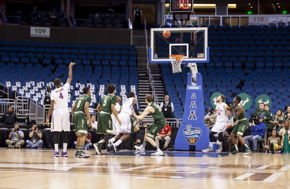 East Carolina's Prince Williams (#4 in white) attempts a three in their 71-66 loss to USF on Thursday at the Amway Center, Orlando, Florida.