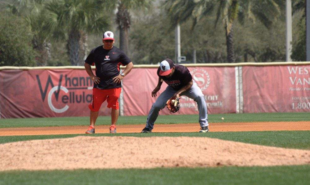 Shortstop Kevin Santa completes a fielding drill as Tampa Bay Spartans coach Joe Urso looks on at the University of Tampa Baseball Field, Tampa, Fla.